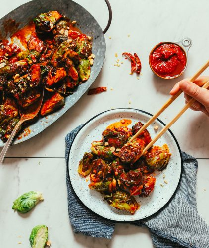 Using chopsticks to grab a bite of our Gochujang Stir-Fried Brussels Sprouts recipe