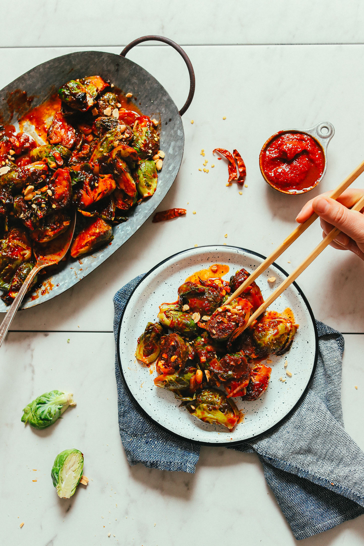 A plate and platter of our vegan Gochujang Stir-Fried Brussels Sprouts