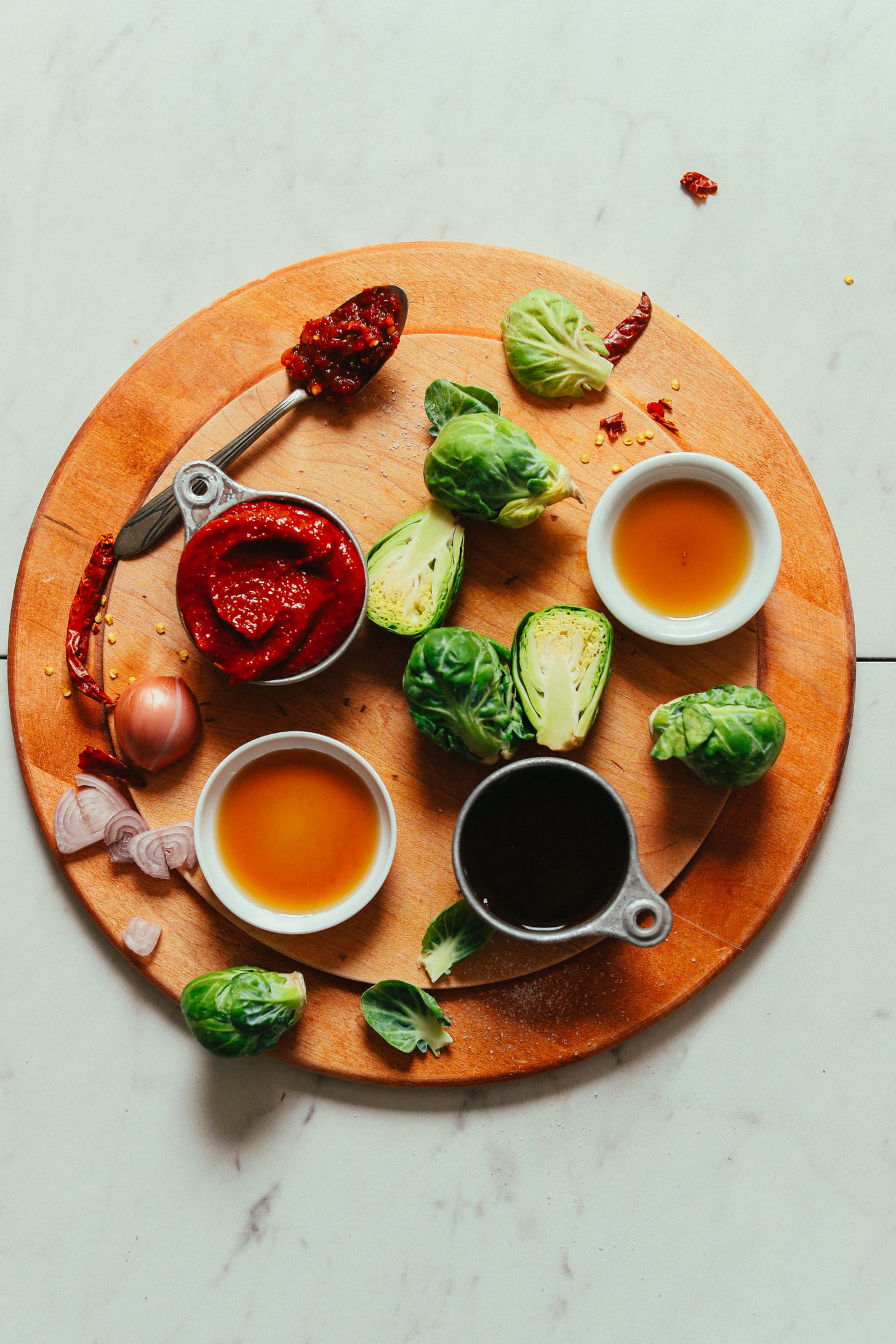 Cutting board with ingredients for making our vegan Gochujang Stir-Fried Brussels Sprouts