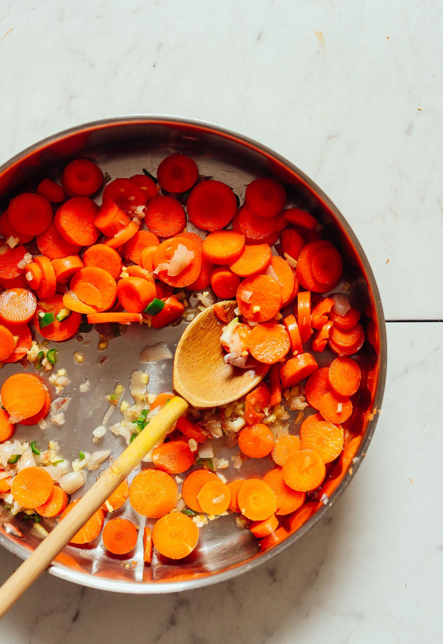 An overhead shot of sautéed carrots, shallot, ginger, garlic, and serrano pepper
