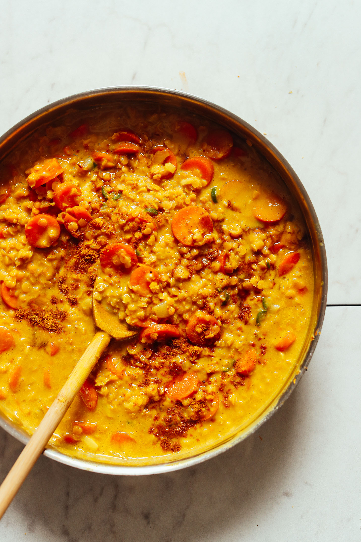 An overhead shot of golden curried lentil soup with carrots, coconut milk, and curry powder