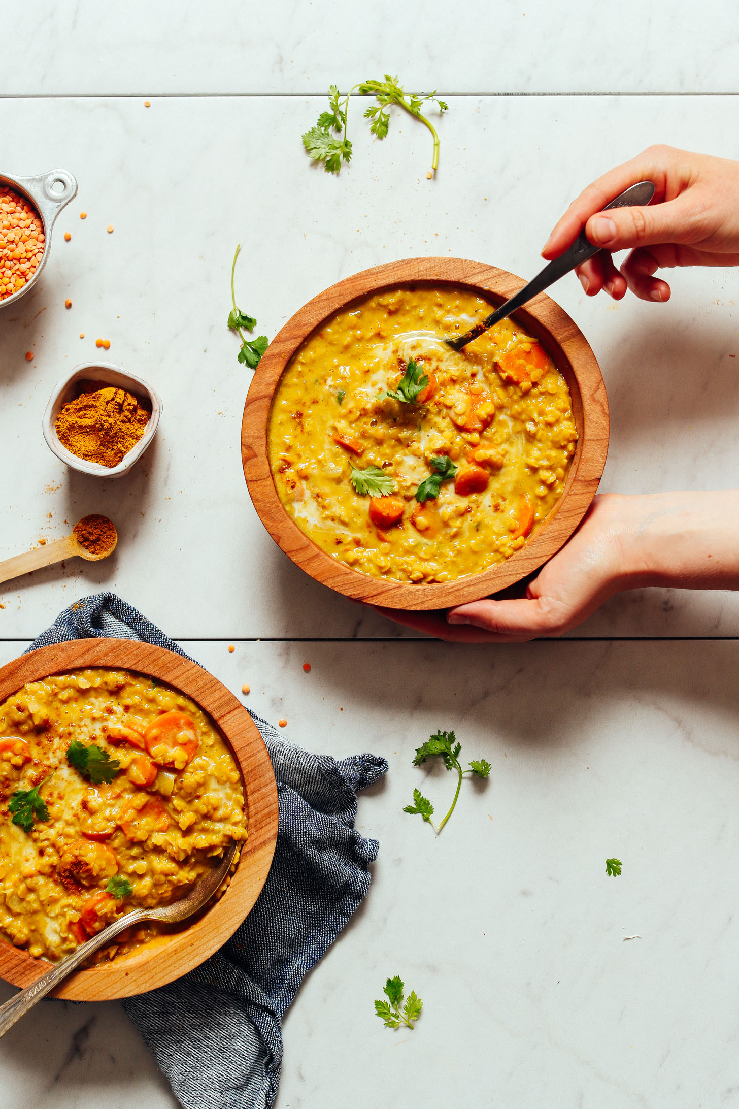 An overhead shot of two bowls of golden curried lentil soup with hands holding one bowl and taking a scoop
