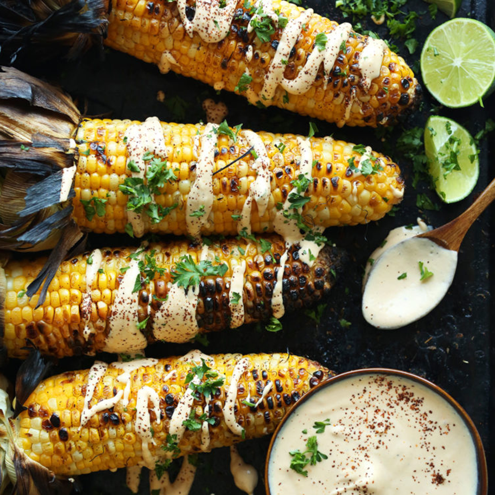 Four ears of grilled corn with sriracha aioli for our 30 Easy Plant-Based Summer Recipes roundup