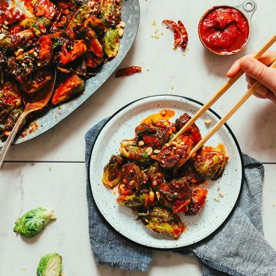 Using chopsticks to grab a bite of Gochujang Brussels Sprouts from a plate