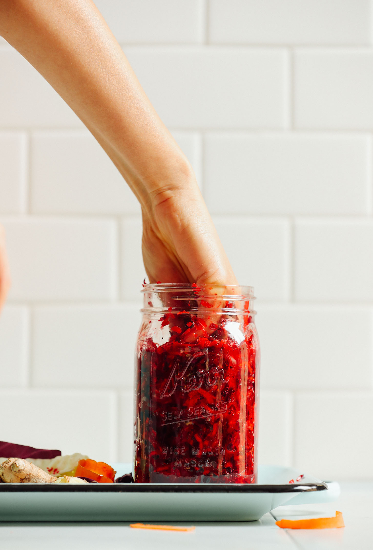 Pressing down on the vegetables inside a jar of sauerkraut