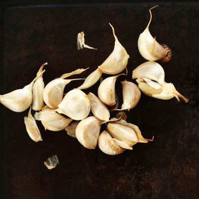 Freshly roasted cloves of garlic on a baking sheet