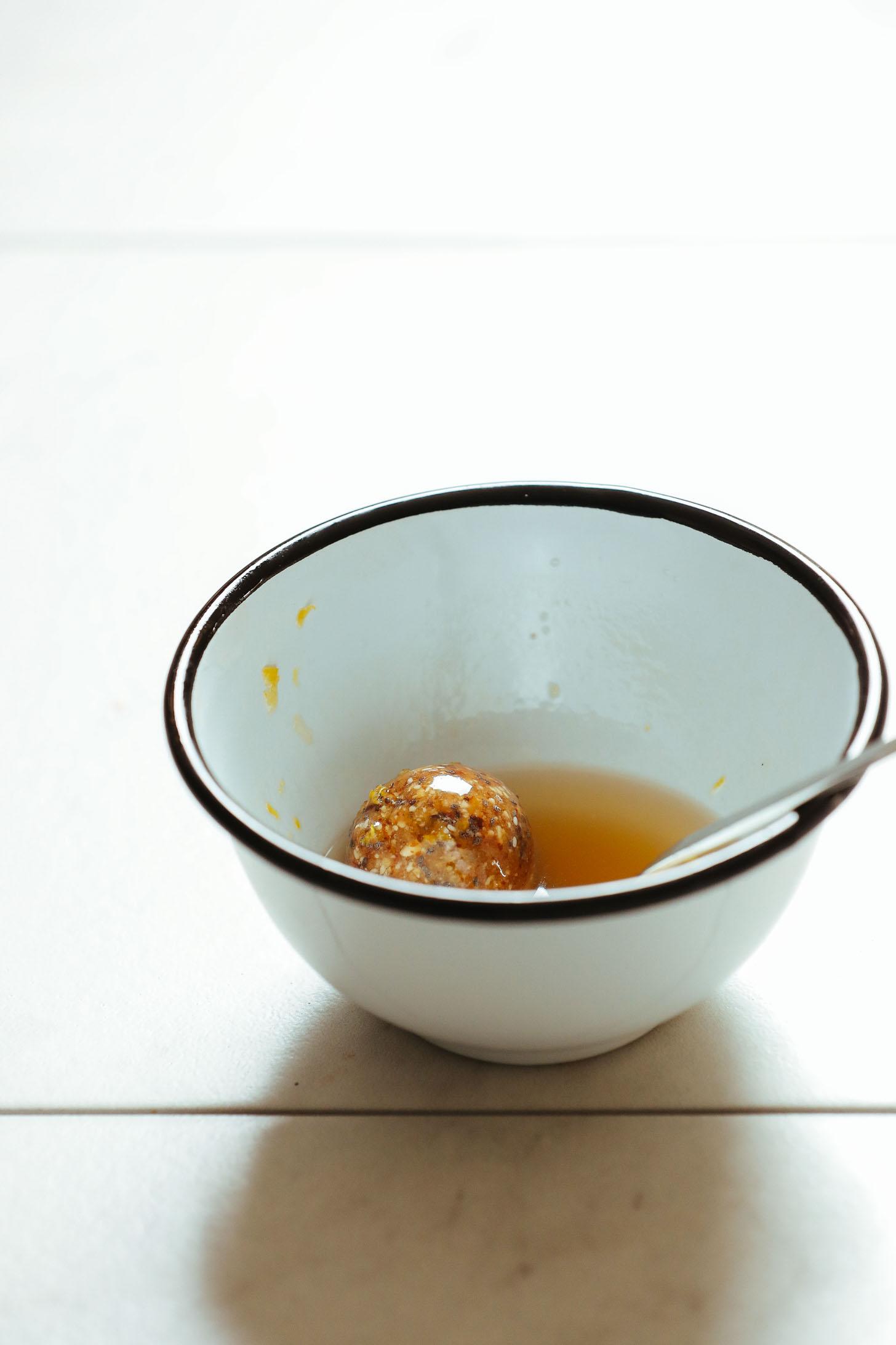 Coating a Vegan Lemon Poppy Seed Donut Hole with glaze