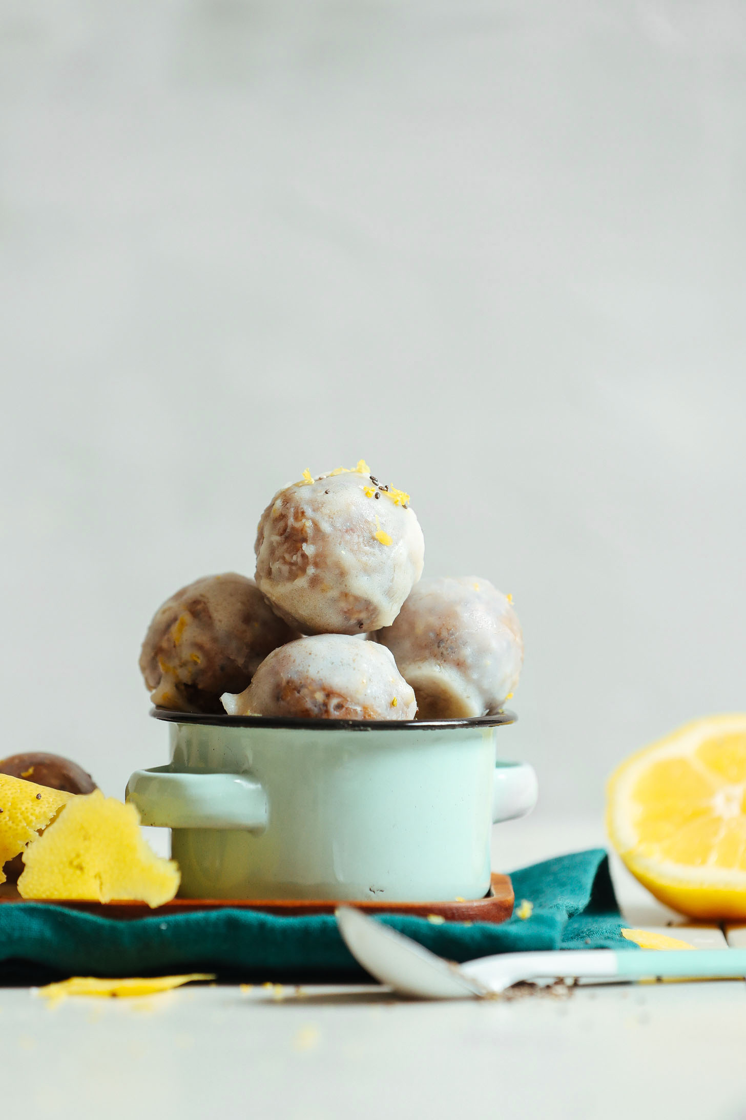 A small blue bowl with no bake vegan donut holes that are scented with lemon zest, lemon juice, and poppy seeds.