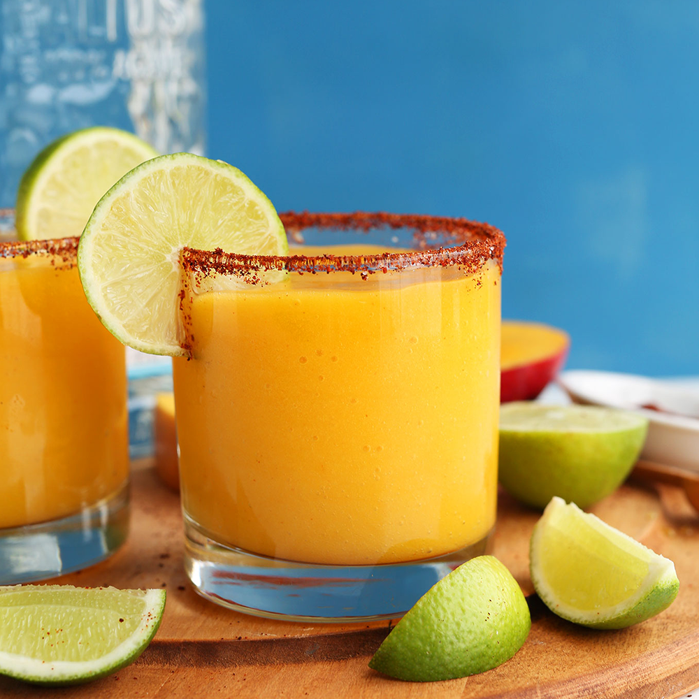 Lime wedges and Mango Chili Lime Margaritas on a cutting board for our roundup of Easy Plant-Based Summer Recipes