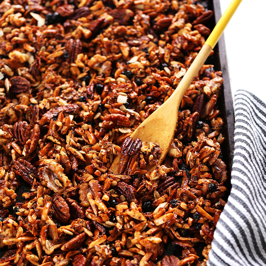 Wooden spoon resting on a baking sheet of freshly baked Grain-Free Granola