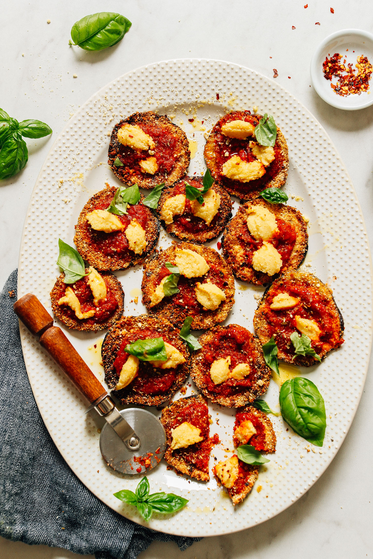Platter filled with crispy vegan Mini Eggplant Pizzas
