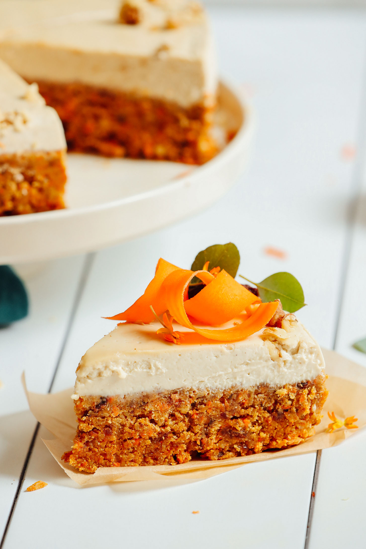 Close up shot of a slice of Raw Vegan Carrot Cake with vegan cream cheese frosting