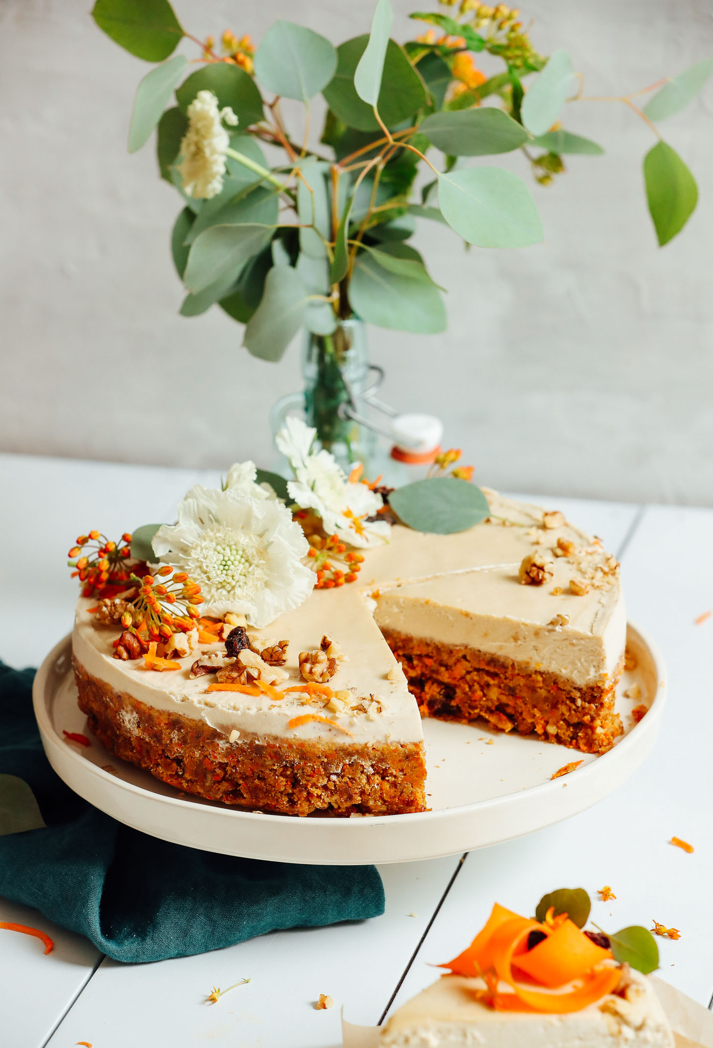 Raw Vegan Carrot Cake decorated with flowers, walnuts, shredded carrots, and raisins