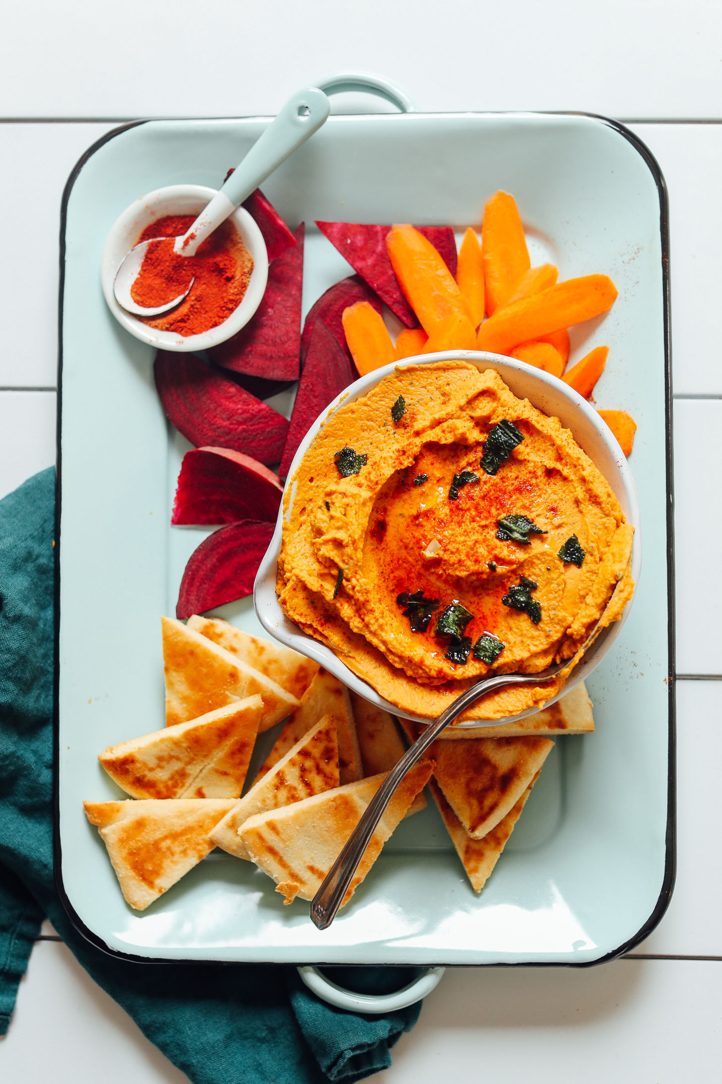 Tray with a bowl of our White Bean Pumpkin Hummus recipe with beet, carrot, and pita for dipping