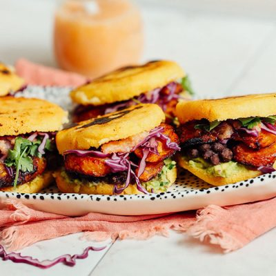 Tray of Vegan Arepa Sandwiches with a jar of hot sauce in the background