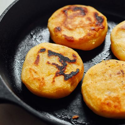 Homemade arepas cooking in a cast-iron skillet