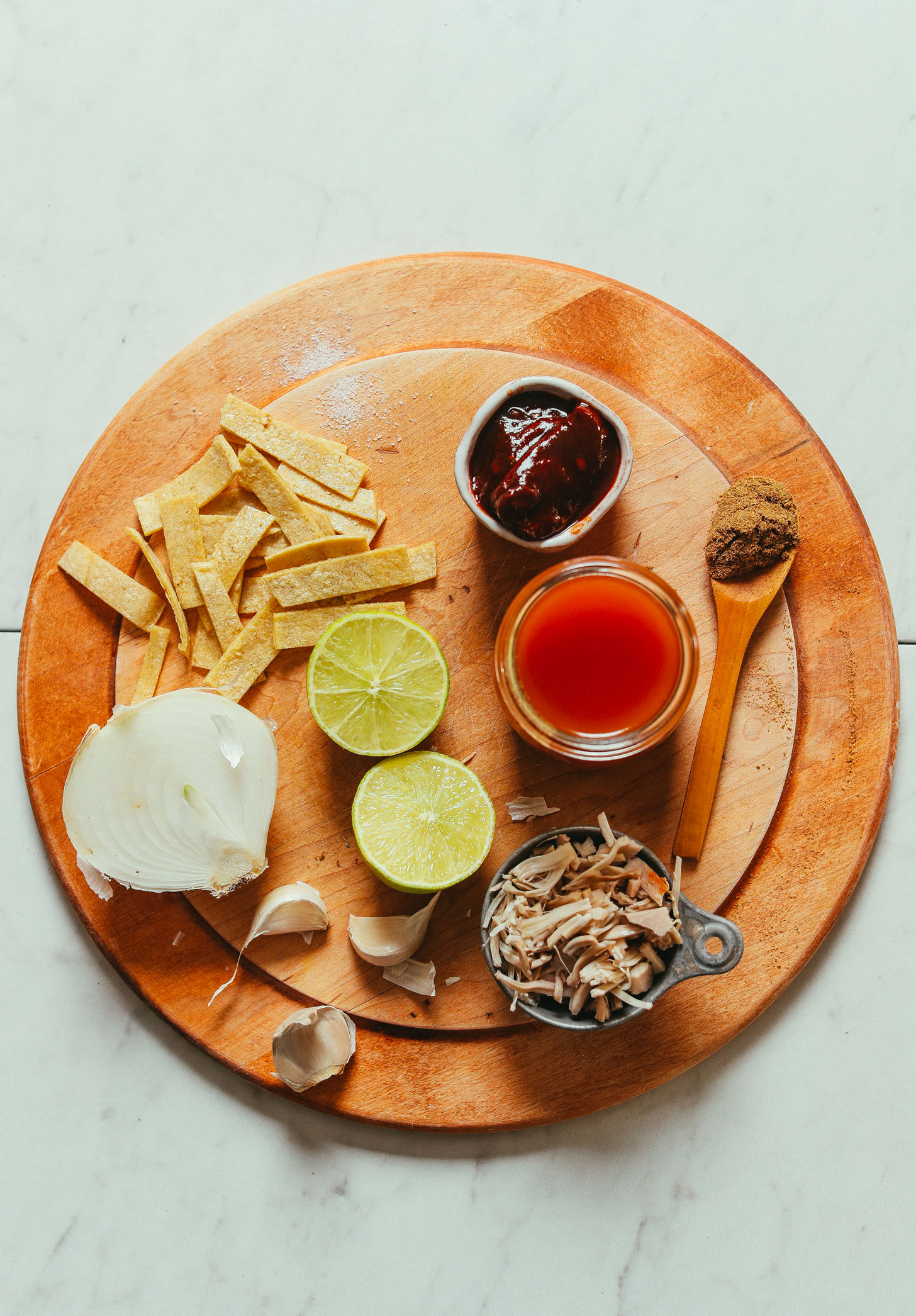Wood cutting board filled with ingredients for making our Vegan Jackfruit Tortilla Soup recipe