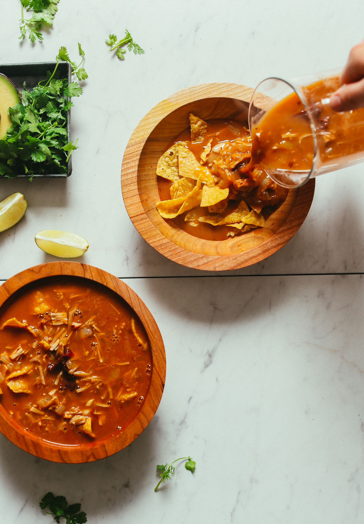 Pouring soup over tortilla chips for Vegan Tortilla Soup with Jacfruit