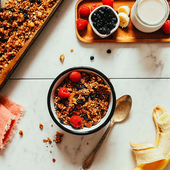 Bowl of vegan Buckwheat Granola alongside fresh fruit, dairy-free milk, and a baking sheet with more granola
