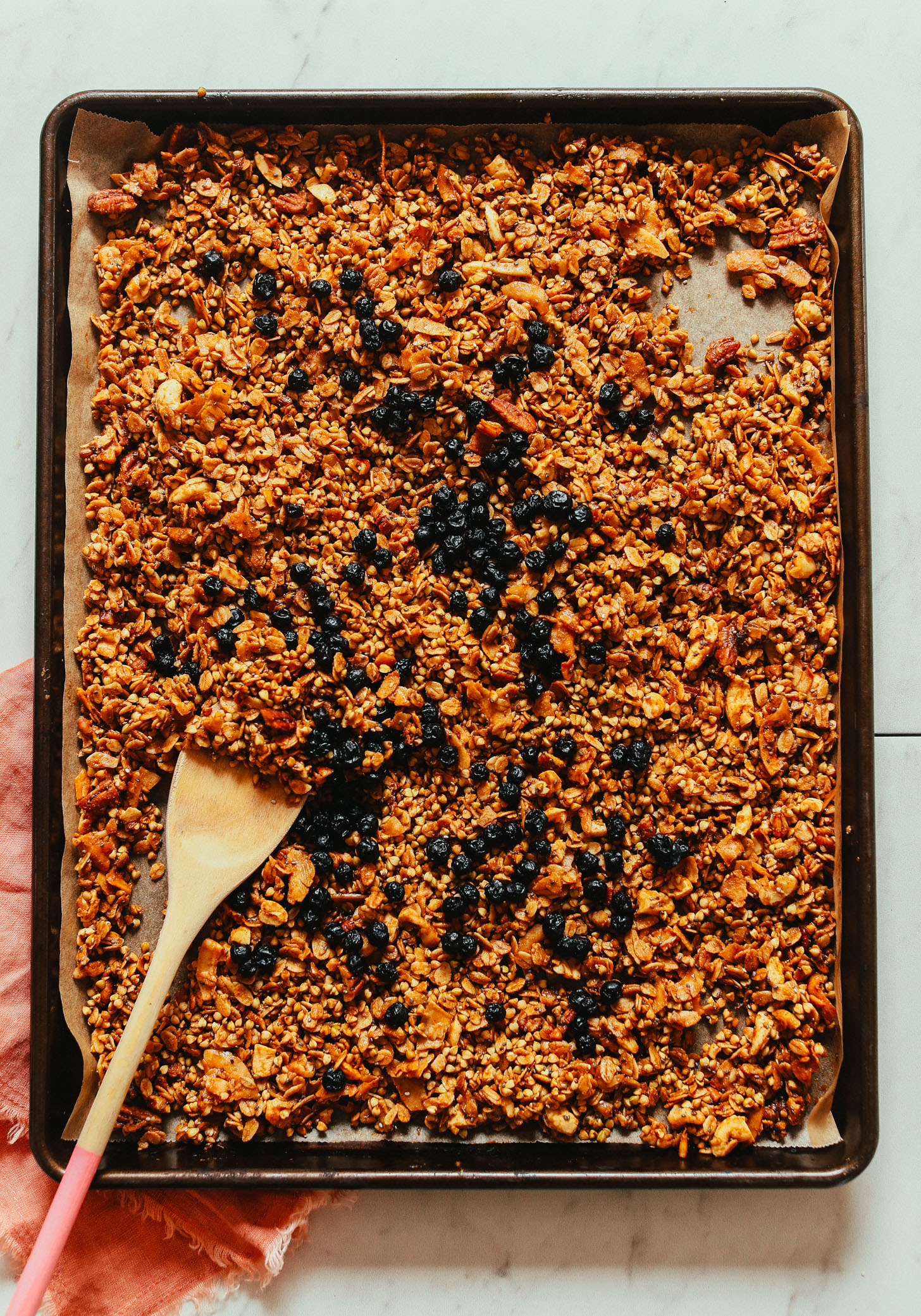 Freshly baked Easy Buckwheat Granola on a parchment-lined baking sheet