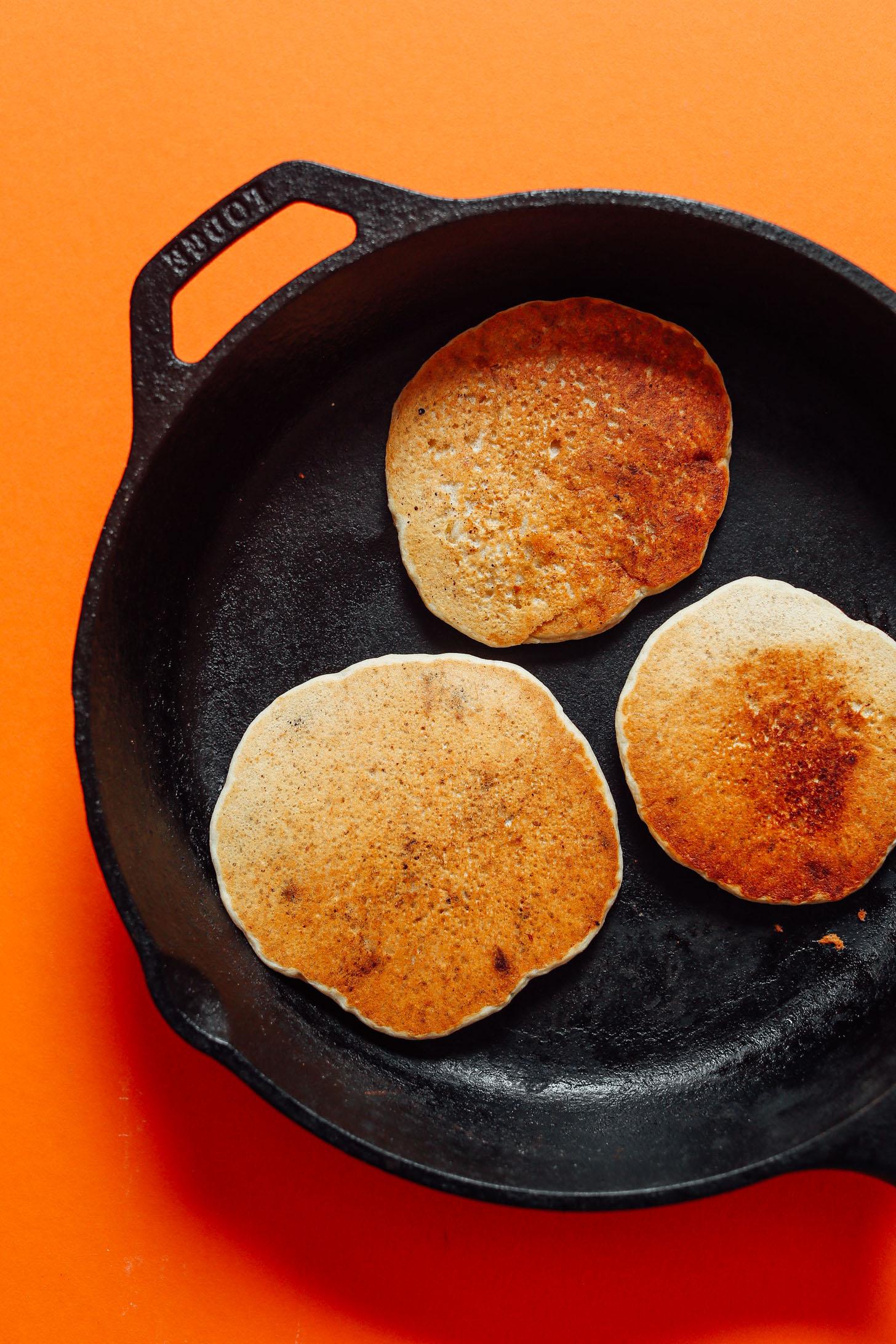 Cooking gluten-free vegan Banana Oat Pancakes in a skillet