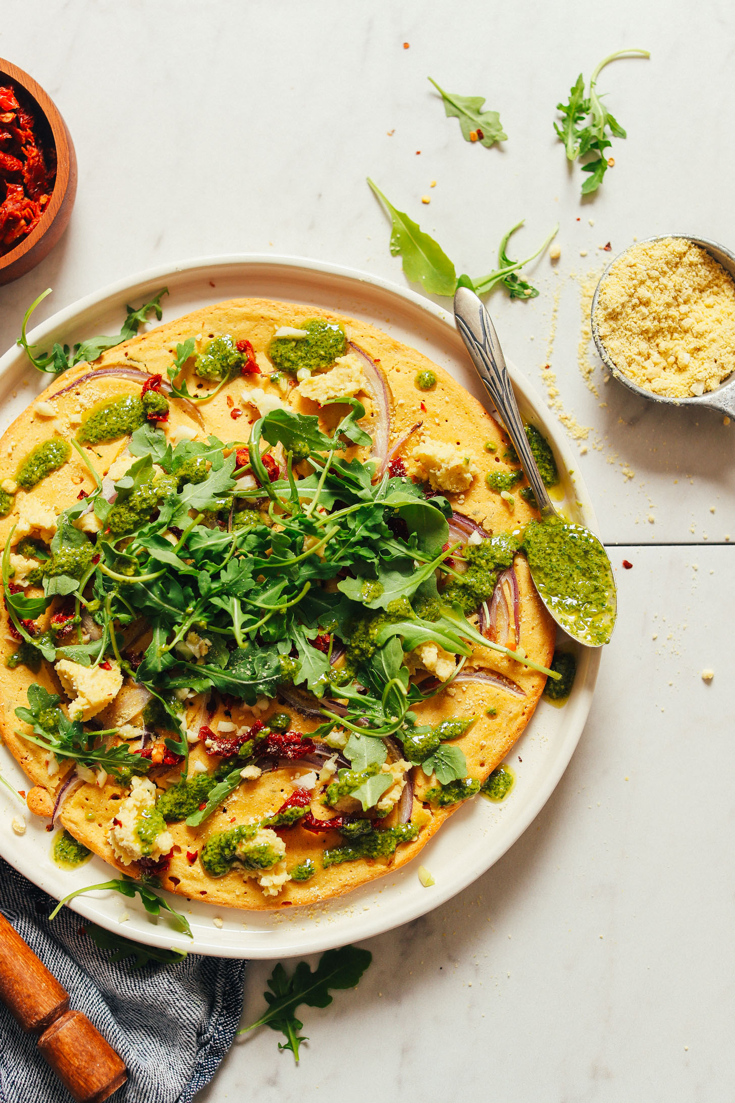 Plate filled with a beautiful gluten-free vegan Socca Pizza with pesto, sun-dried tomatoes, and arugula