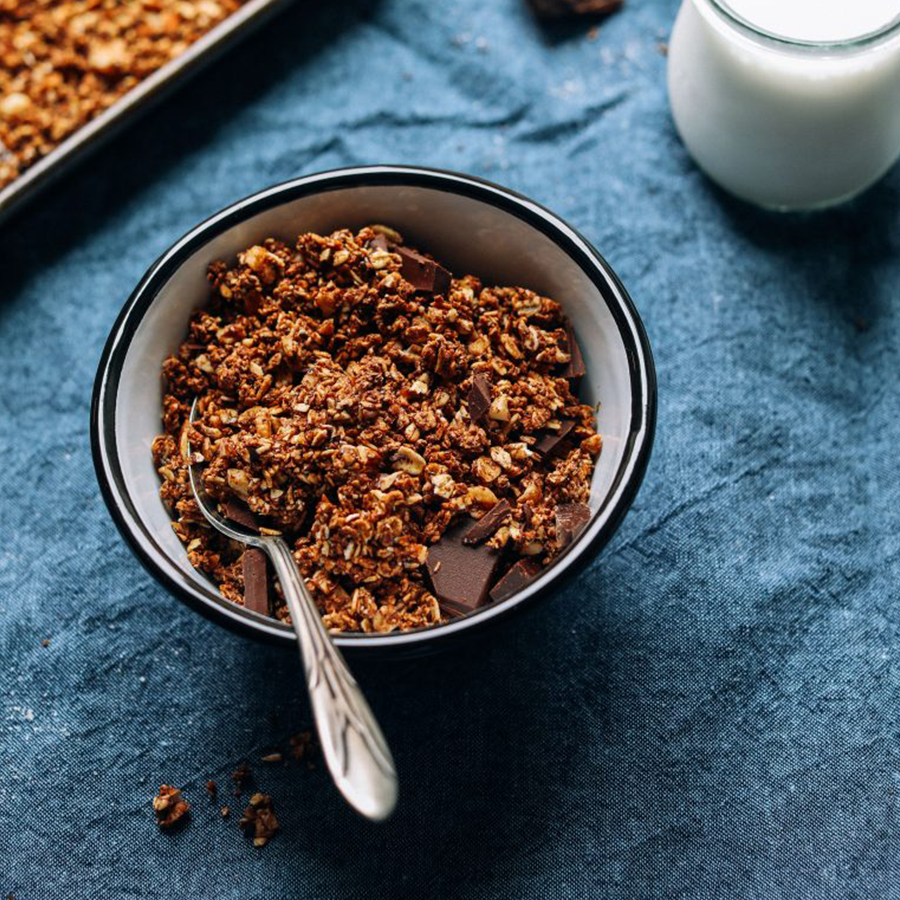 Bowl of Dark Chocolate Granola and jar of dairy-free milk for serving