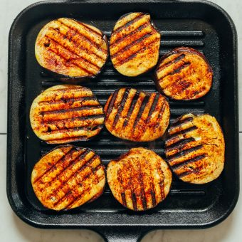 Griddle pan filled with smoky sliced eggplant