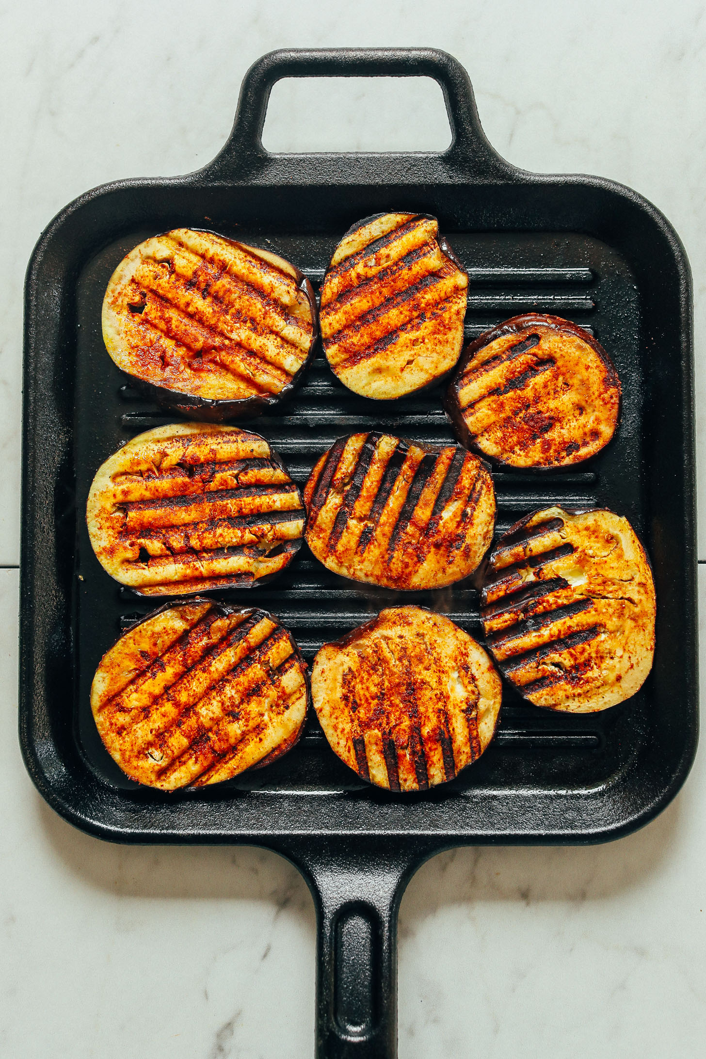 A overhead shot of eggplant slices seasoned with a spice blend and grill marks.