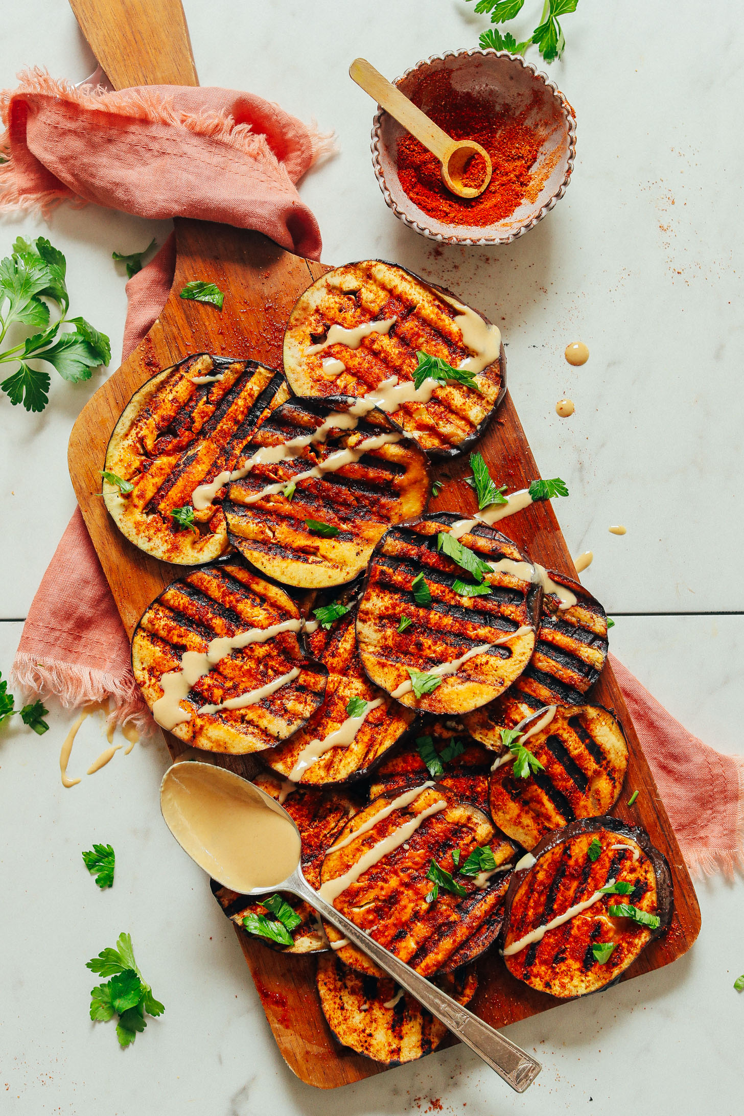 An overhead shot of simple grilled eggplant slices drizzled with tahini dressing and spice blend.