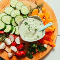 Bowl of Creamy Vegan Ranch dressing surrounded by fresh chopped vegetables for dipping