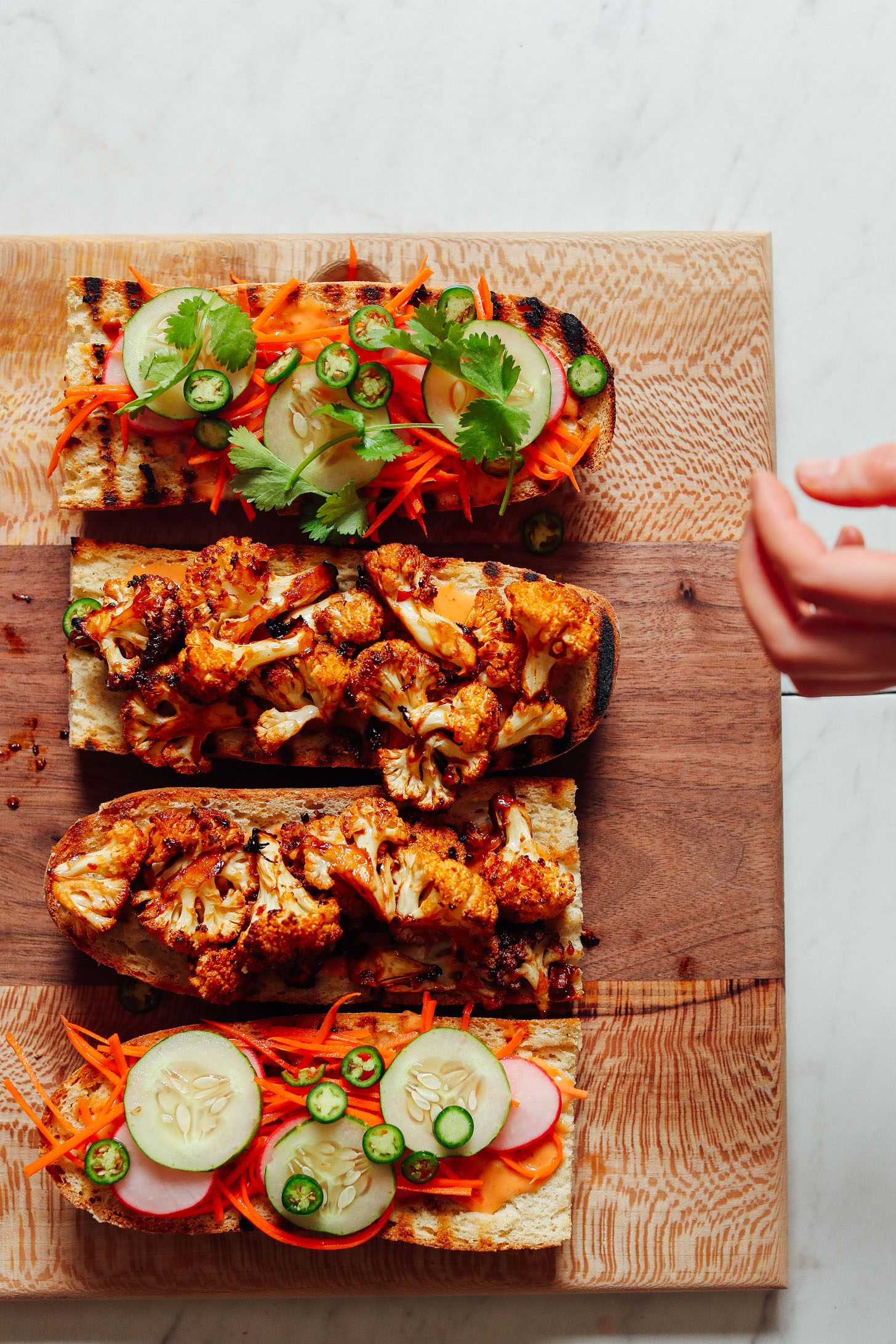 Open-faced Cauliflower Banh Mi sandwiches resting on a wood cutting board