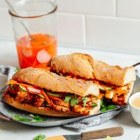 Two Cauliflower Banh Mi sandwiches on a plate with pickled veggies in a jar
