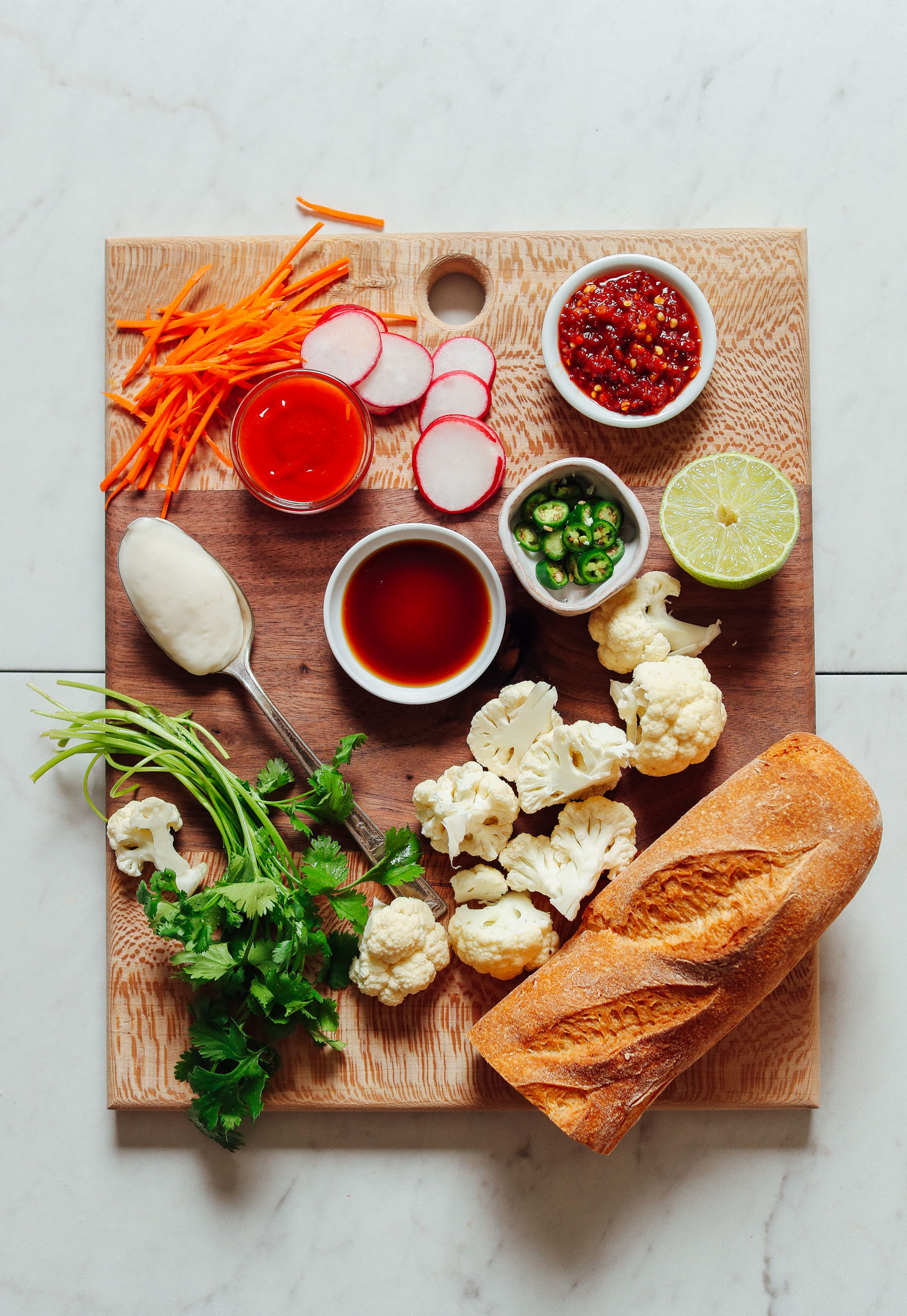 Wood cutting board filled with ingredients for making our Cauliflower Banh Mi recipe