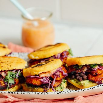 Tray of Vegan Arepa Sandwiches with Plantains, Black Beans, Guacamole, and a jar of habanero hot sauce
