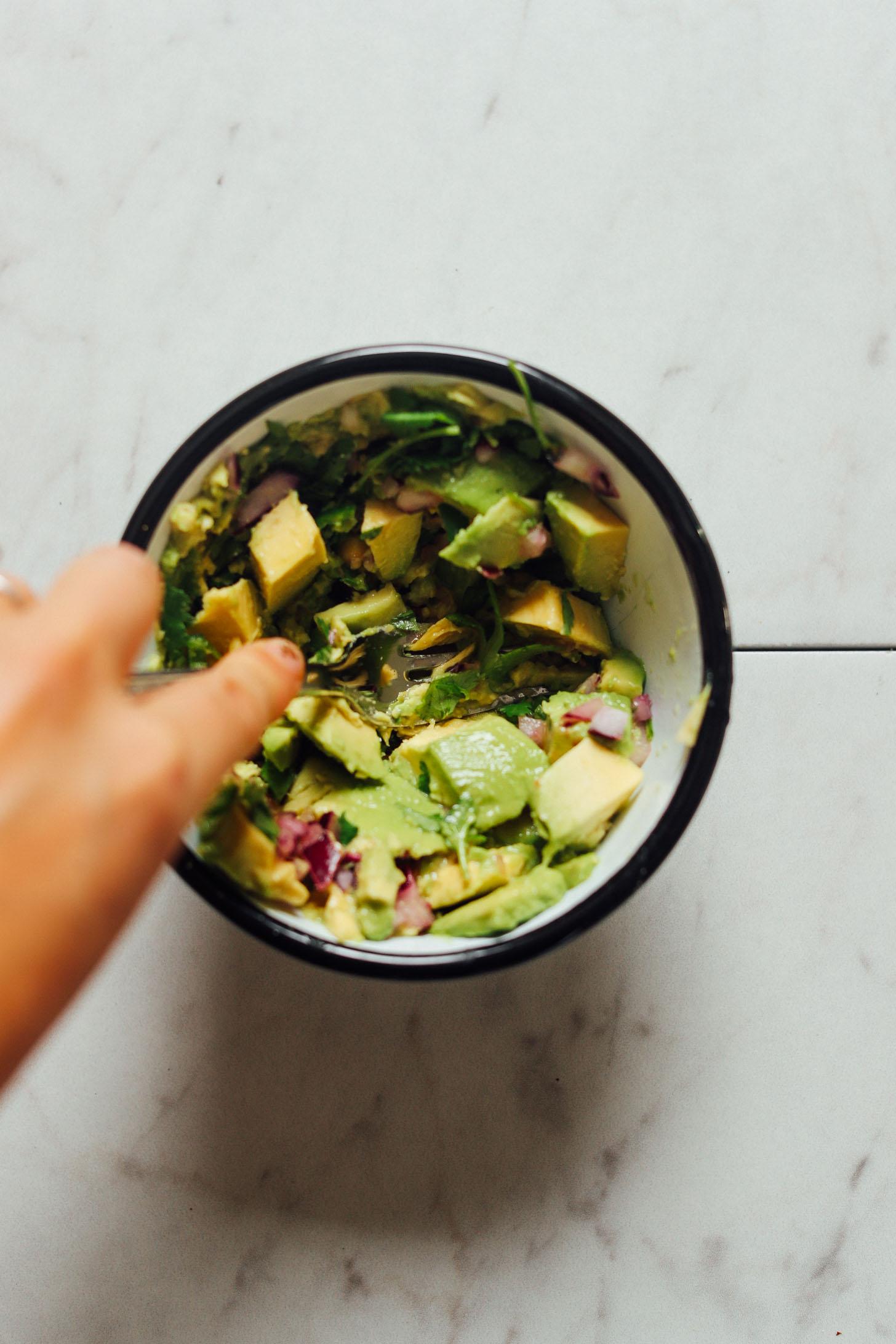 Using a fork to mash avocado for homemade vegan guacamole