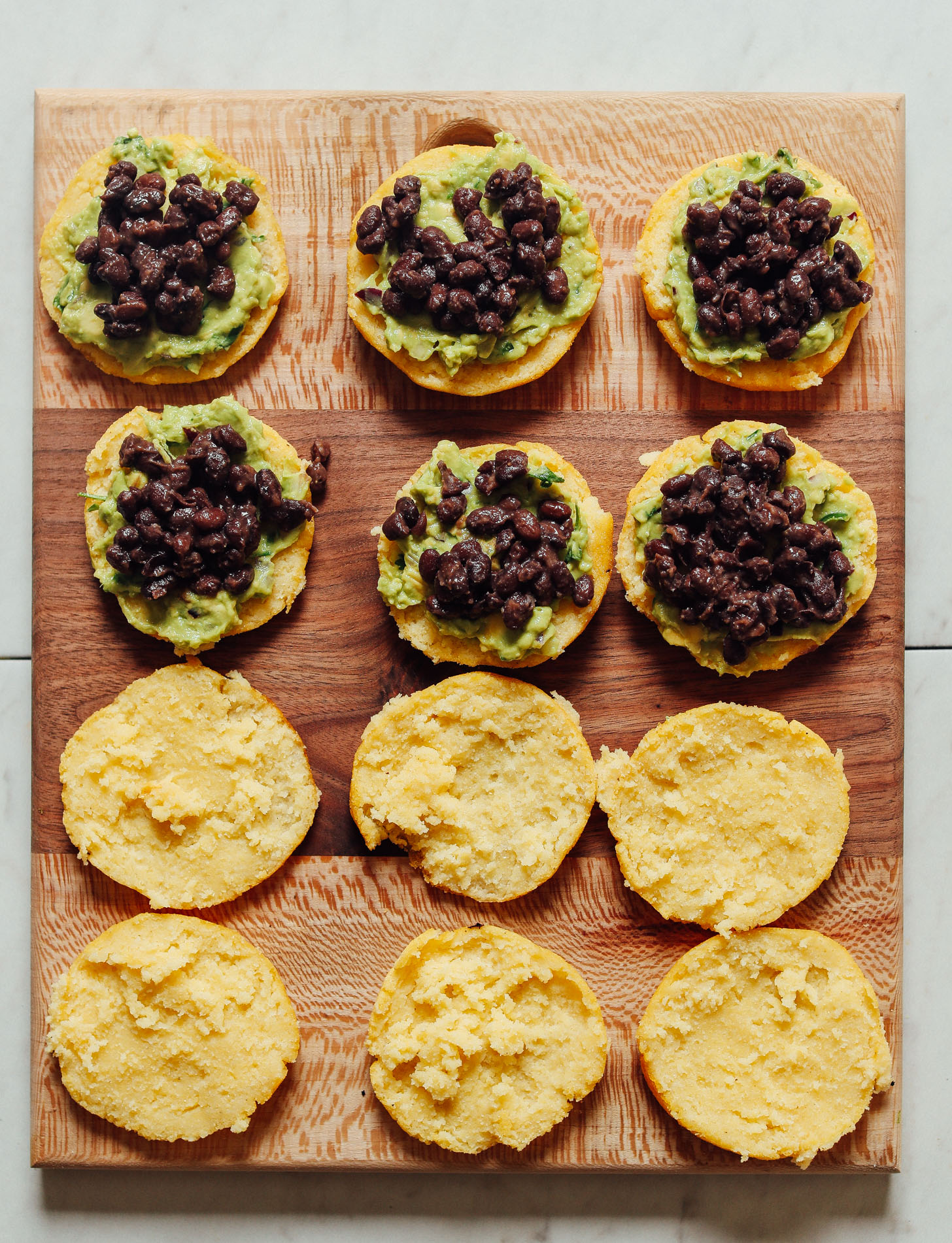 Wood cutting board with open-faced Arepa Sandwiches topped with guacamole and black beans