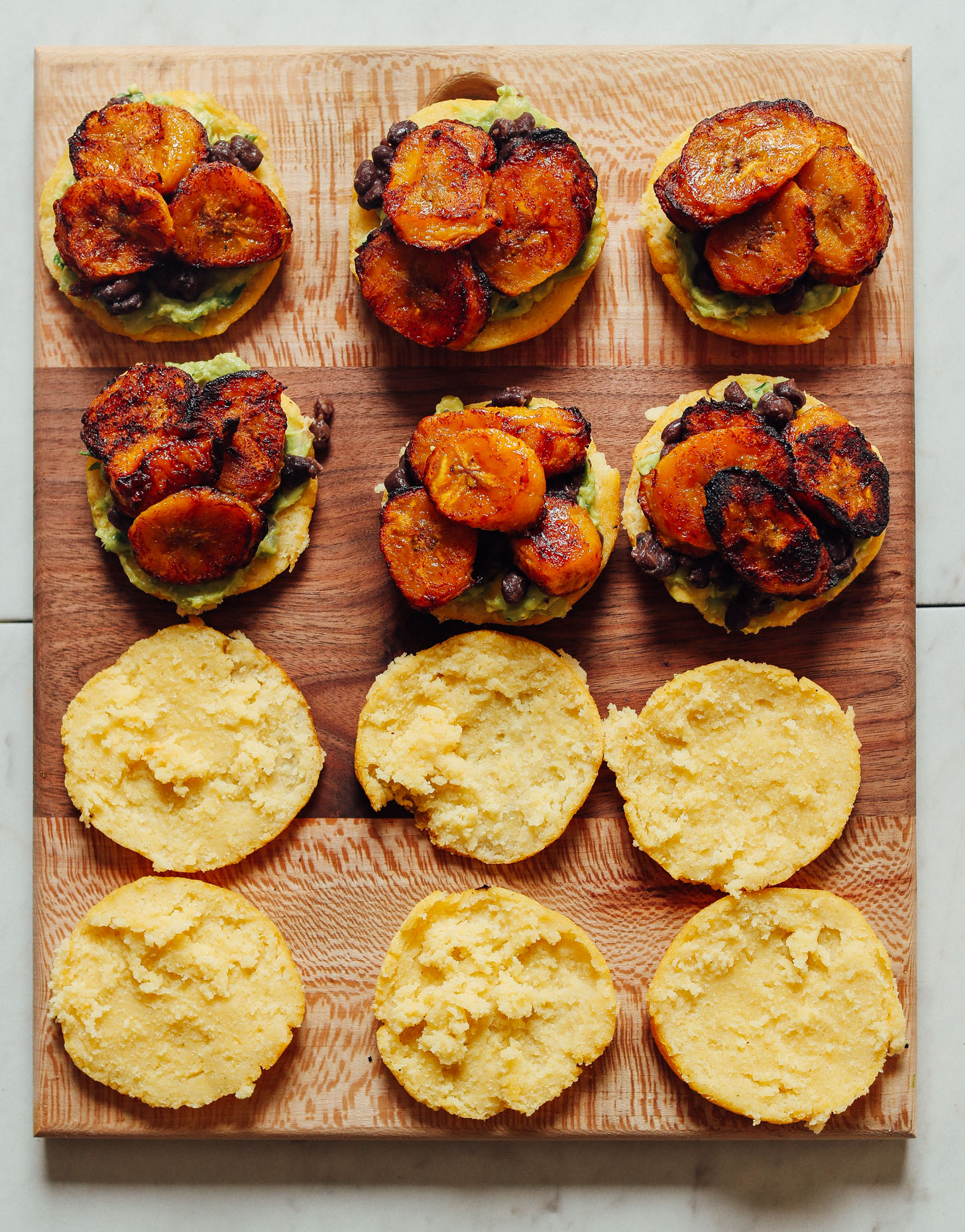 Open-faced Vegan Arepa Sandwiches topped with guacamole, black beans, and plantains