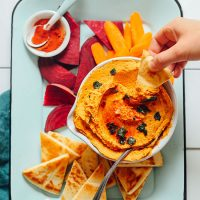 Dipping a slice of pita bread into a bowl of our Pumpkin Hummus recipe