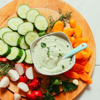 Wood cutting board filled with veggies and a bowl of our Creamy Vegan Ranch Dressing