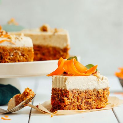 Partially eaten slice of Raw Carrot Cake resting beside the rest of the cake