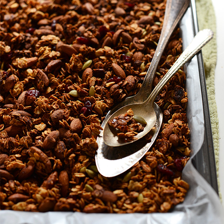 Spoons resting on a parchment-lined baking sheet of Sweet Potato Granola