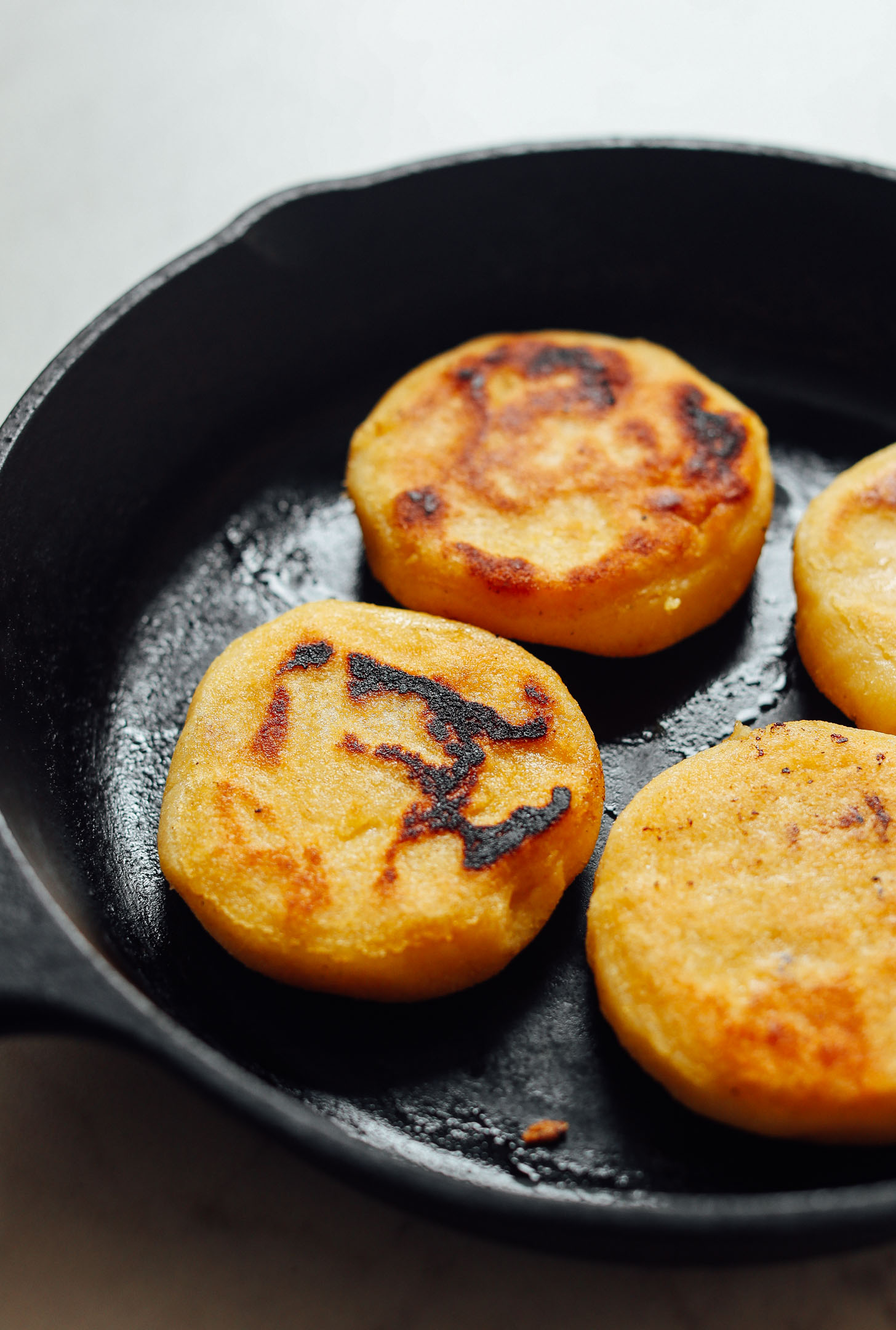 Cooking homemade gluten-free Arepas in a cast-iron skillet