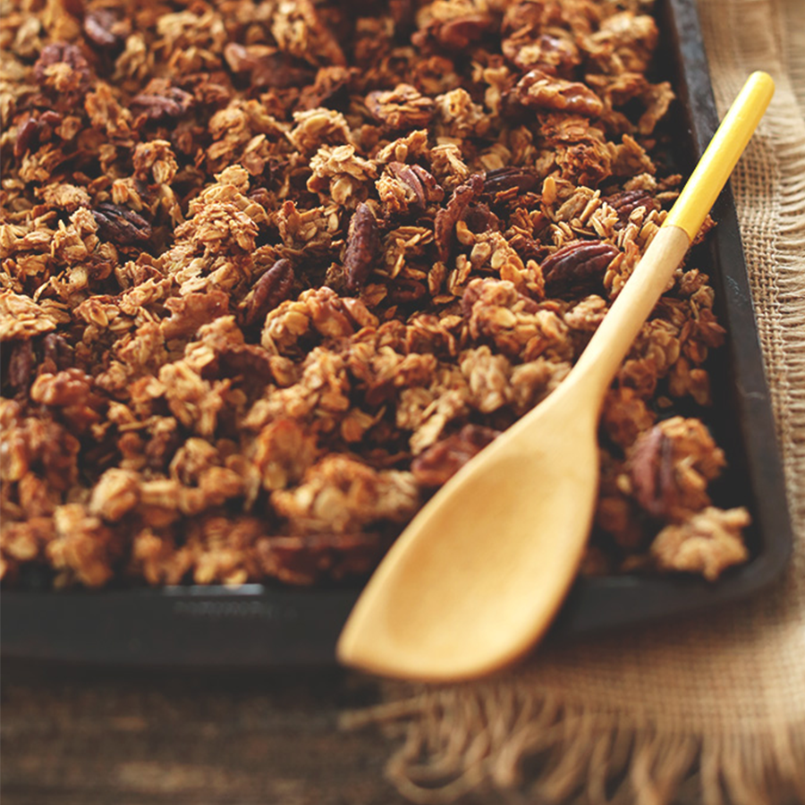 Wooden spoon resting on a tray of Vegan Banana Bread Granola