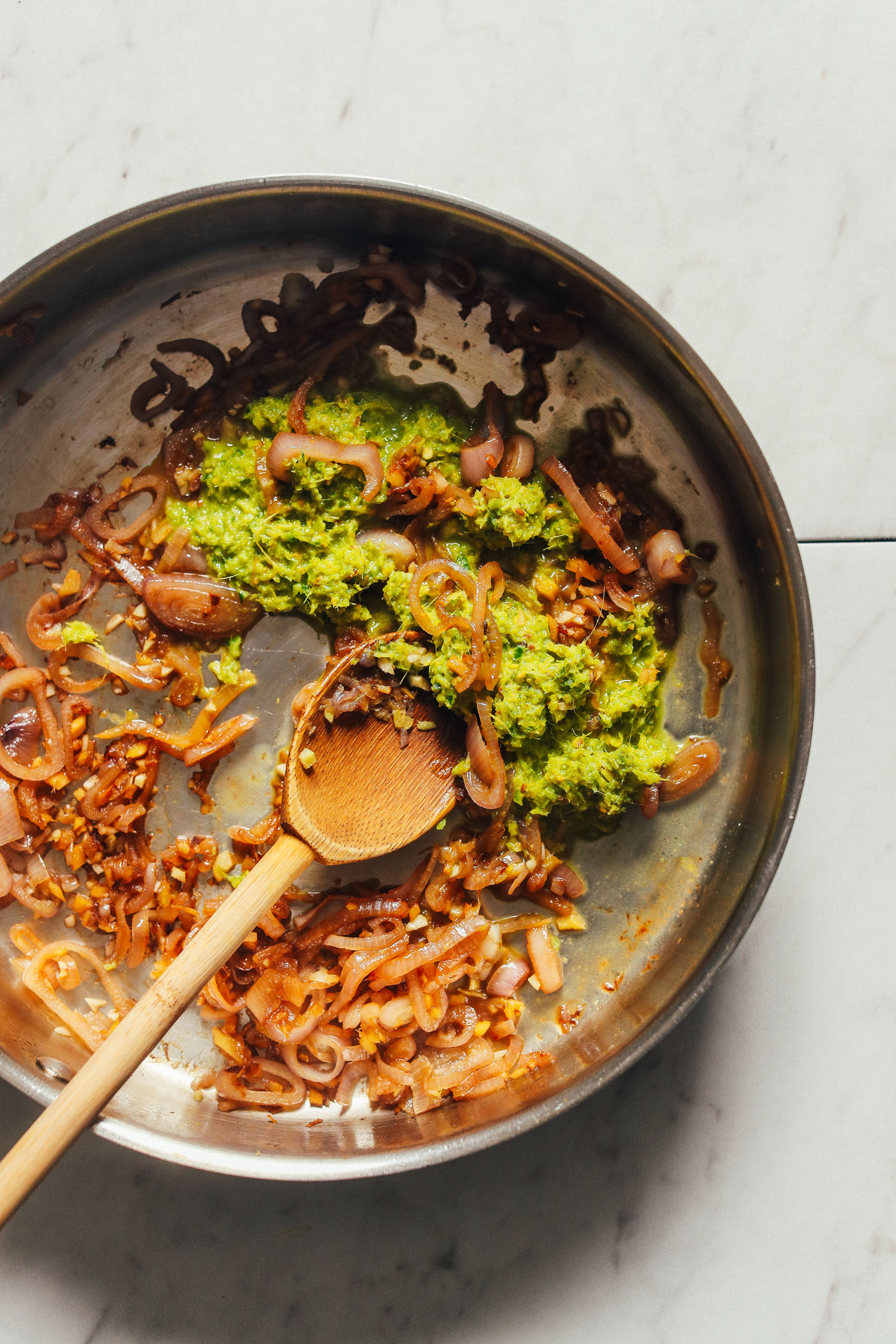 Overhead image of a pan with sautéed onion, garlic, and green curry paste with a wooden spoon stirring the ingredients
