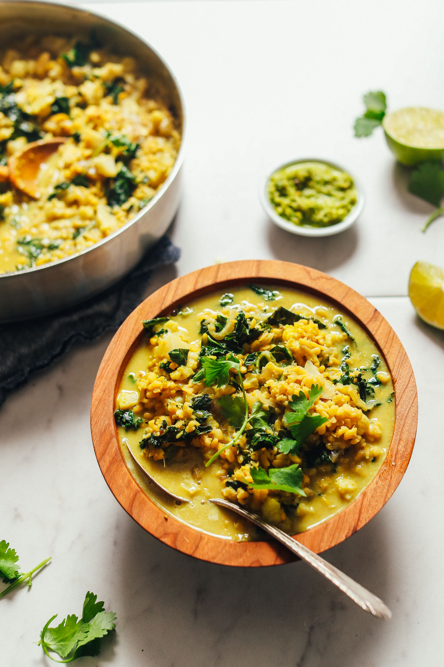 Image of green curry with kale and lentils in a wooden bowl with metal spoon