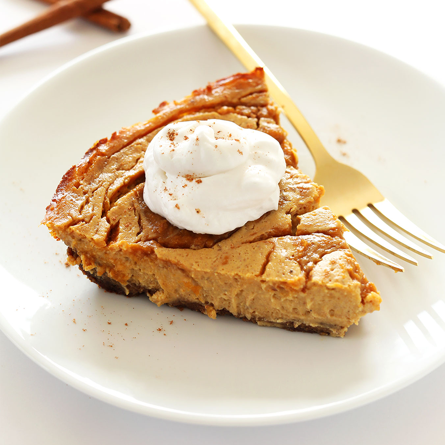 Plate with a slice of Pumpkin Swirl Cheesecake topped with coconut whipped cream