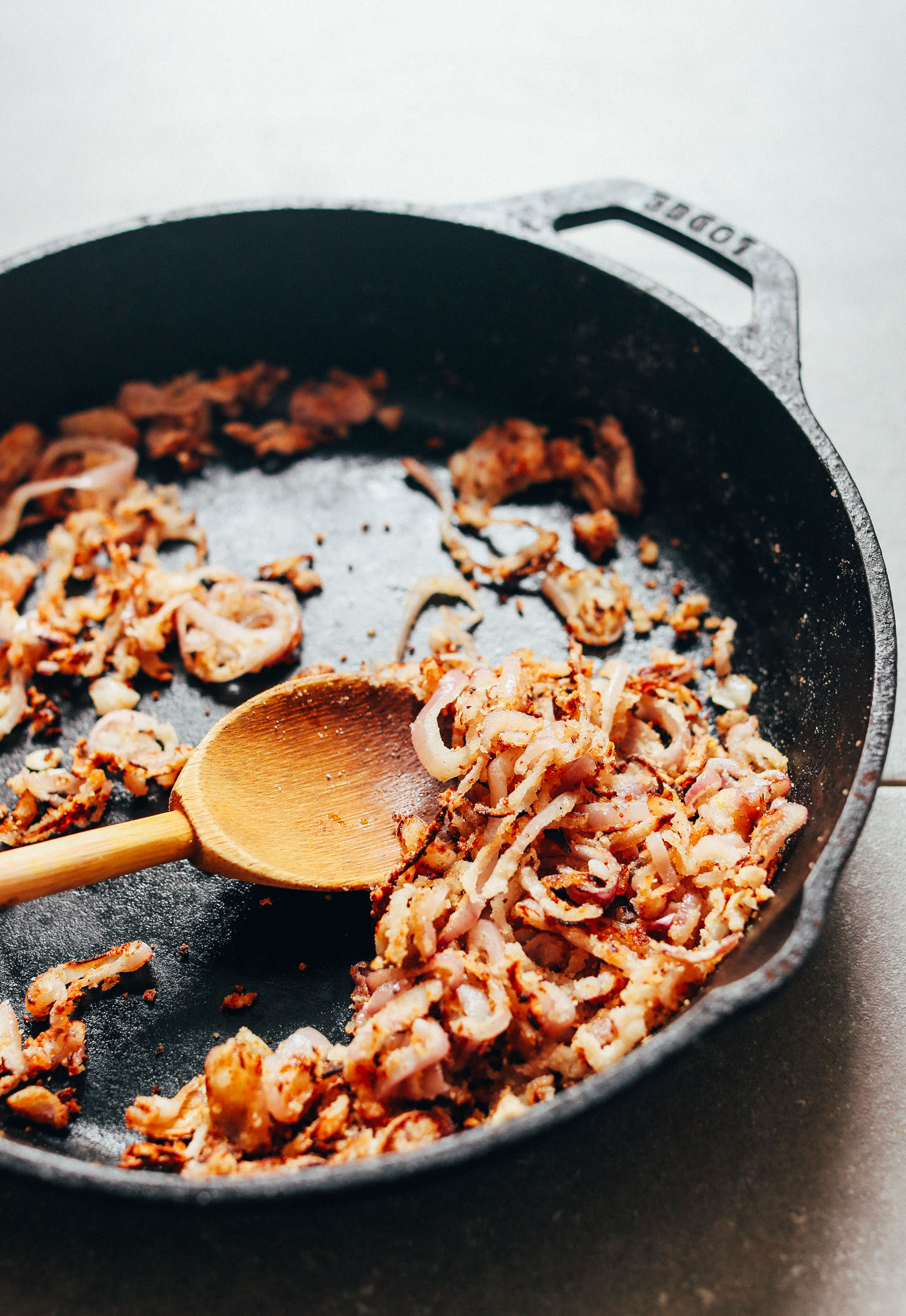 Batch of crispy shallots cooking in a cast-iron skillet