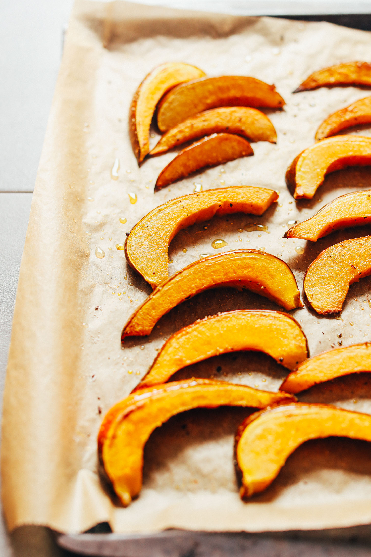 Roasted acorn squash slices on a parchment-lined baking sheet