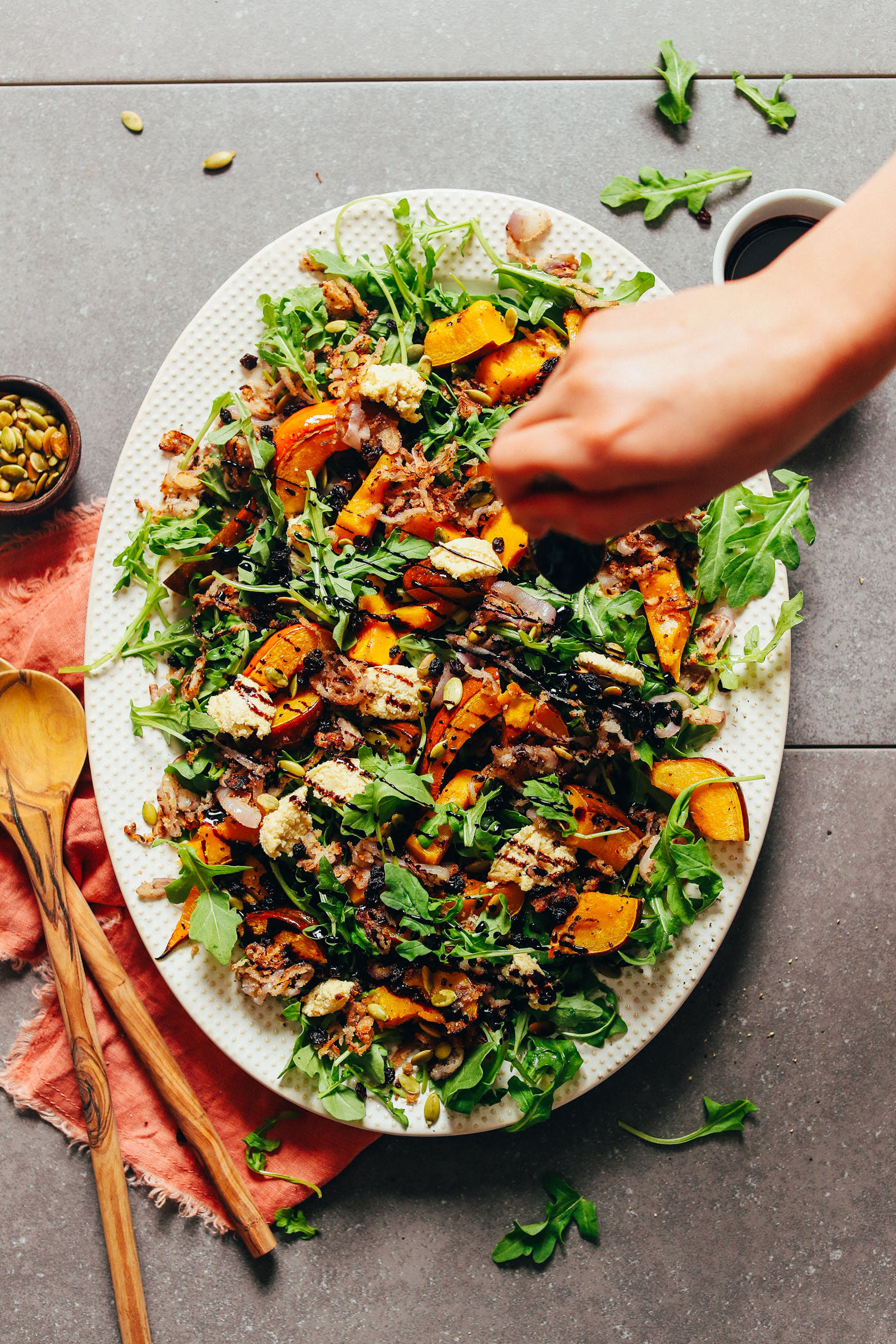 Adding balsamic drizzle over our Roasted Squash Salad with Nut Cheese